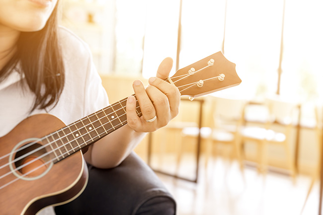 woman handicraft playing ukulele